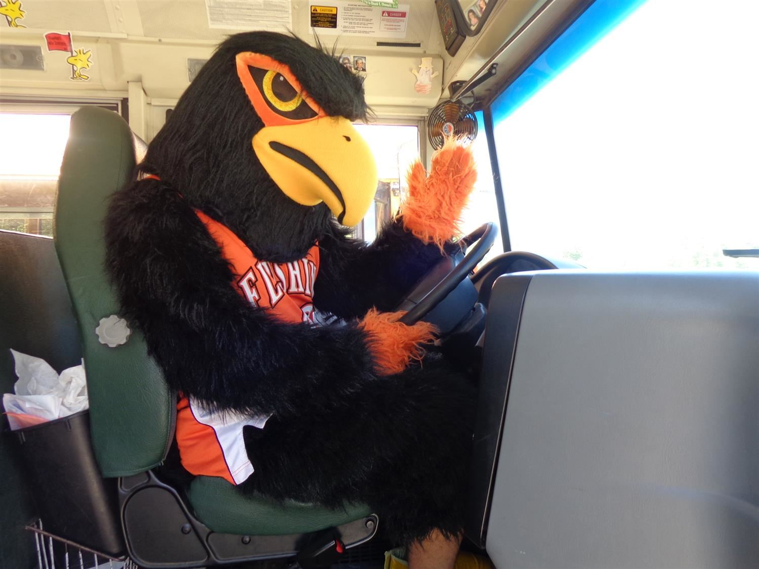 Flushing Raider Mascot driving a bus